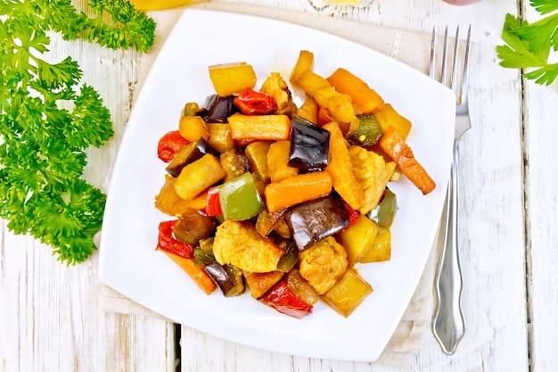 Braten sie fleisch, zucchini, auberginen, karotten und paprika mit honig, sojasauce und rotwein in einem teller auf einer serviette vor dem hintergrund der holzbretter oben