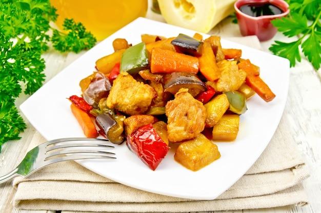 Braten sie fleisch, zucchini, auberginen, karotten und paprika mit honig, sojasauce und rotwein in einem teller auf serviette vor dem hintergrund von holzbrettern