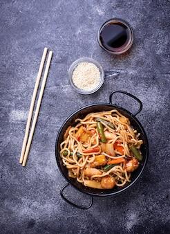 Braten sie nudeln mit hühnchen, tofu und gemüse.