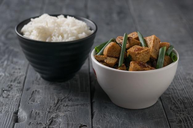 Braten sie tofu in einer weißen schüssel und reis in einer schwarzen schüssel auf einem holztisch. vegetarisches asiatisches gericht.
