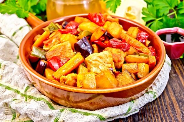 Braten von fleisch, zucchini, auberginen, karotten und paprika mit honig, sojasauce und rotwein in einer pfanne auf einem handtuch auf dem hintergrund von holzbrettern