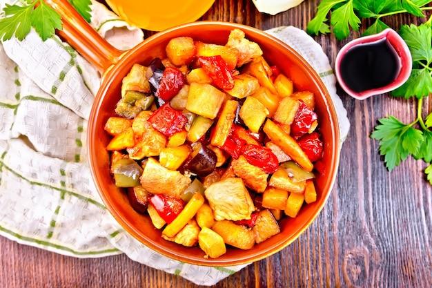 Braten von fleisch, zucchini, auberginen, karotten und paprika mit honig, sojasauce und rotwein in einer pfanne auf serviette vor dem hintergrund der holzbretter oben plan