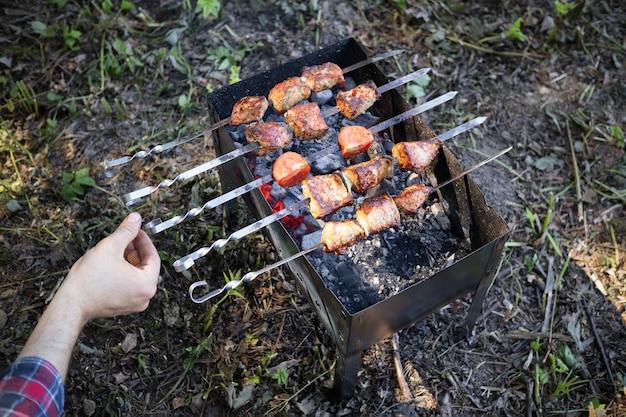 Braten von kebabs auf spießen und metallpfanne auf dem boden und der hand des kochmanns, ansicht von oben.