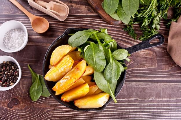 Bratkartoffel mit kräutern und gewürzen auf dem holztisch. draufsicht. Premium Fotos