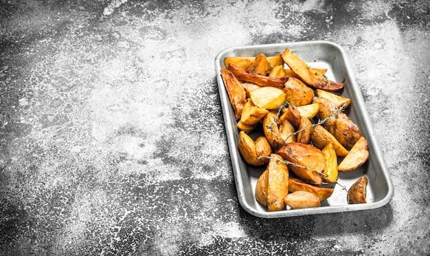 Bratkartoffeln auf backblech mit gewürzen und kräutern auf rustikalem tisch.