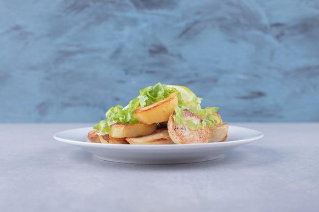 Bratkartoffeln garniert mit zitrone auf weißem teller.