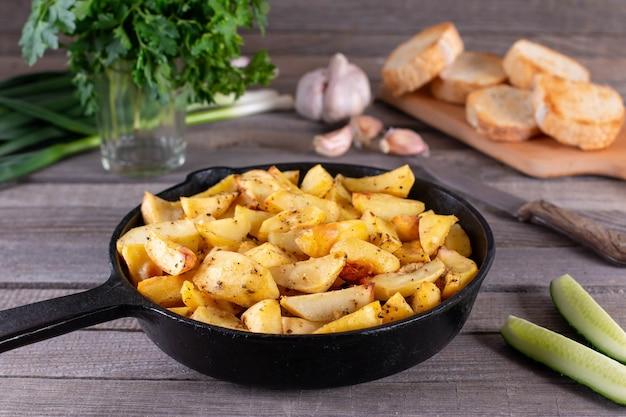 Bratkartoffeln im ländlichen stil mit gewürzen und frischem grün. auf rustikaler pfanne, auf einem holztisch. bratkartoffeln