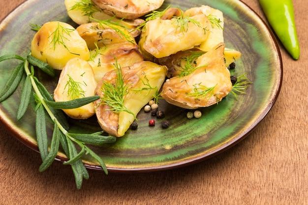 Bratkartoffeln mit dill und rosmarin auf einer grünen keramikplatte