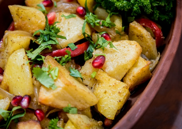 Bratkartoffeln mit fleischstücken in einem tontopf. europäische küche.