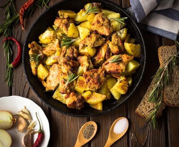 Bratkartoffeln mit hühnchen in einer gusseisernen pfanne