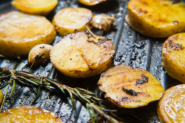 Bratkartoffeln mit knoblauch und rosmarin in einer pfanne.
