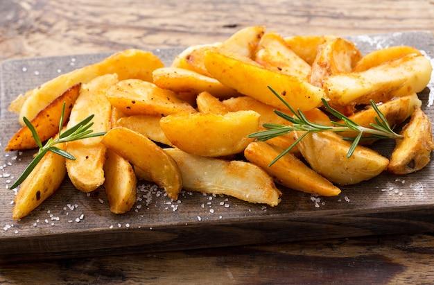 Bratkartoffeln mit rosmarin auf holzbrett