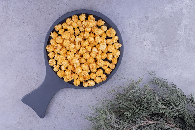 Bratpfanne gefüllt mit karamellbeschichtetem popcorn neben immergrünen zweigen auf marmorhintergrund. foto in hoher qualität