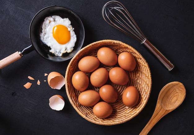 Bratpfanne in den eiern und in den rohen eiern auf hintergrund