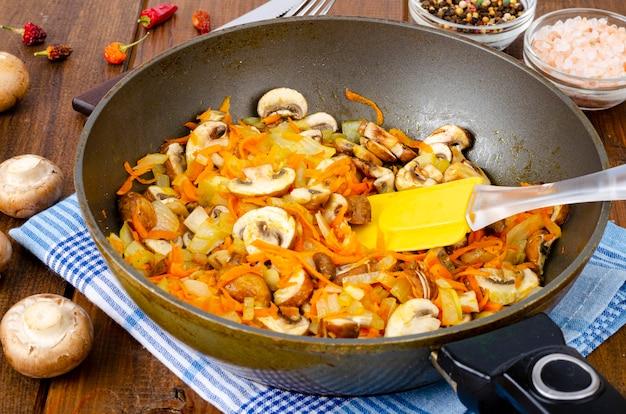 Bratpfanne mit champignons, zwiebeln und karotten mit gebratenen pilzen auf holztisch.