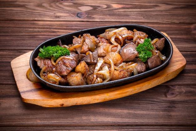 Bratpfanne mit gebratenem fleisch und zwiebeln