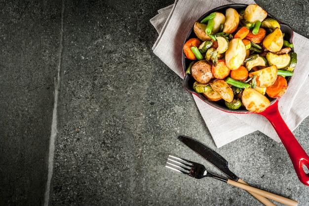 Bratpfanne mit gebratenem saisonherbstgemüse (zucchini, kartoffeln, karotten, bohnen), auf schwarzer steintischplatteansicht