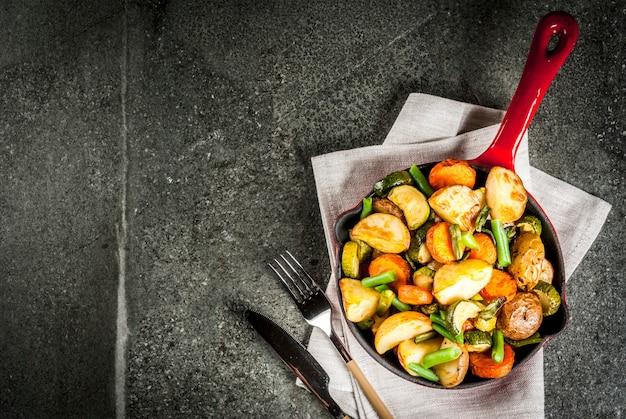 Bratpfanne mit gebratener saisonherbstgemüsezucchini, kartoffeln, karotten, bohnen, auf schwarzer steintischplatteansicht