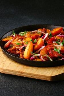 Bratpfanne mit kartoffelfleisch und zwiebel auf schwarzem betonhintergrund
