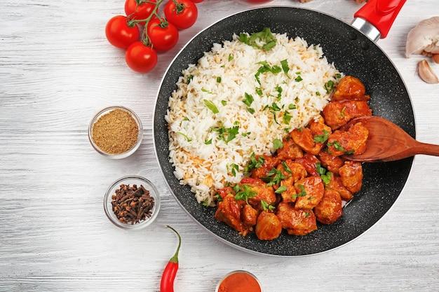 Bratpfanne mit leckerem chicken tikka masala und reis auf holztisch
