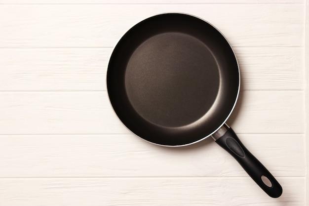 Bratpfanne und auf dem holztisch draufsicht kochen