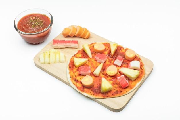 Bratwurst, ananas und krabbenstab auf pizzateig