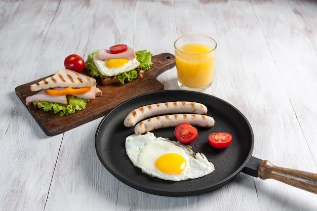 Bratwurst mit ei und gemüse auf pfanne, croissants, orangensaft und sandwiches