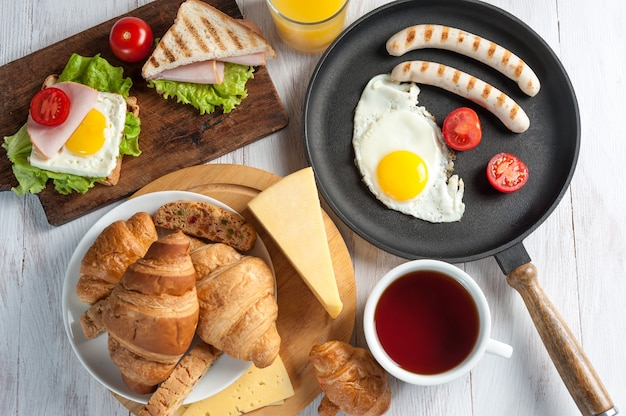 Bratwurst mit ei und gemüse auf pfanne, croissants, tee und sandwiches