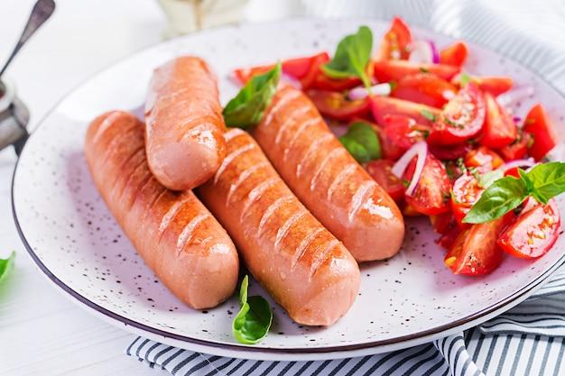 Bratwurst mit tomaten, basilikumsalat und roten zwiebeln