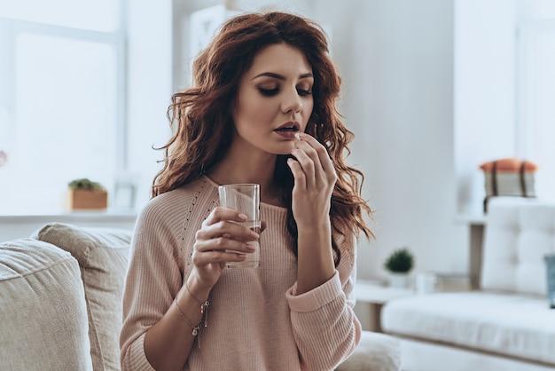Brauche ein paar vitamine. kranke junge frauen fühlen sich schlecht und nehmen tabletten, während sie zeit zu hause verbringen