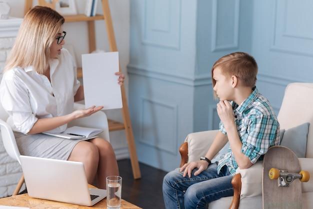 Brauche eine sekunde. junger teenagerpatient, der freizeitkleidung trägt, die seine linke hand nahe kinn hält, während er in der halbstellung sitzt
