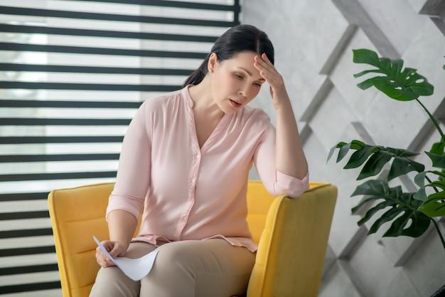 Brauchen sie ärztliche beratung. traurige elende frau in einer rosa bluse und hose, die auf einem stuhl in der nähe des fensters sitzen und mit gesenktem kopf nach unten schauen.