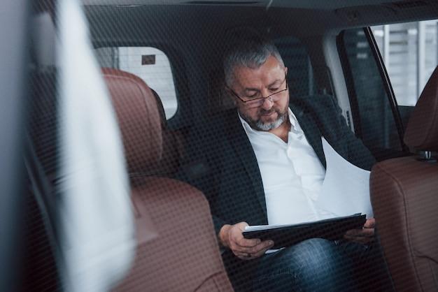 Brauchen sie aufmerksamkeit für details. papierkram auf dem rücksitz des autos. senior geschäftsmann mit dokumenten