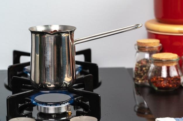 Brauen sie kaffee in einer stahltürke auf einem gasherd nah oben
