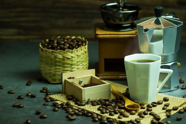 Brauen sie schwarzen kaffee in der weißen tassen- und morgenbeleuchtung. röstkaffeebohnen im bambuskorb.