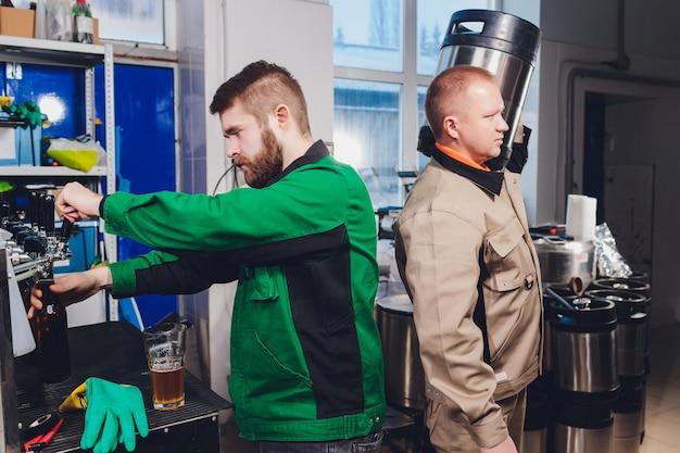 Brauereifabrik, die bier in glasflaschen auf fördererlinien verschüttet. industriearbeit, automatisierte produktion von lebensmitteln und getränken. technologische arbeit in der fabrik.