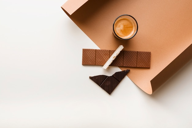 Braun; weißer und dunkler schokoriegel mit kaffeeglas auf papier gegen weißen hintergrund