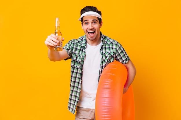 Braunäugiger mann in weißer mütze und kariertem hemd lacht gegen orangefarbenen raum. porträt des kerls im urlaub mit aufblasbarem kreis und einer flasche bier.