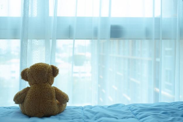 Braunbärpuppe, die auf dem bett sitzt und durch den vorhang und das fenster schaut