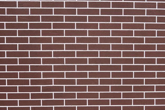 Braune backsteinmauer mit weißen fugenlinien. abstrakter backsteinbeschaffenheitshintergrund. neues haus außen
