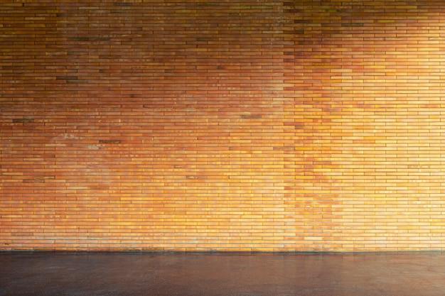 Braune backsteinmauer und betonboden im leeren raum mit fensterlicht. abstrakter hintergrund.