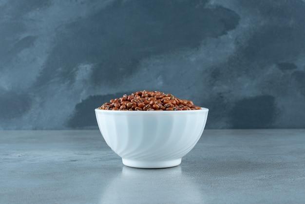 Braune bohnen in einer weißen keramikschale. foto in hoher qualität