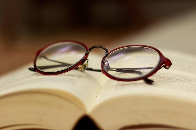 Braune brille setzen sie das buch auf. brauntonhintergrund, kopierraum