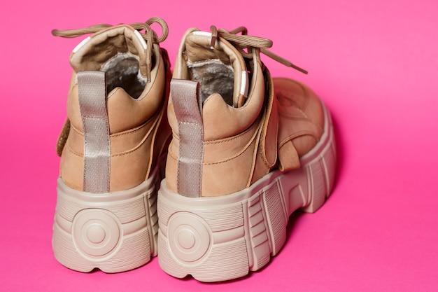 Braune damenschuhe aus leder mit hohen sohlen auf rosafarbenem hintergrund. modeschuhe