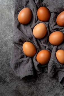 Braune eier auf dunkelgrauem stoff draufsicht flach legen