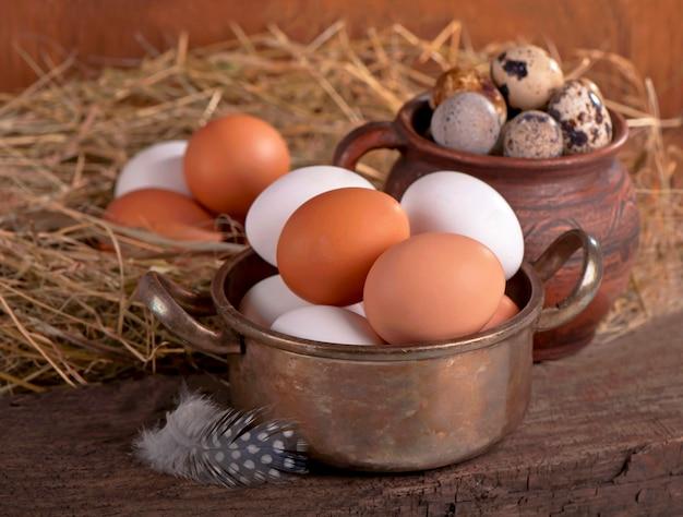 Braune eier im holzkorb. gebrochenes ei mit eigelb im hintergrund.