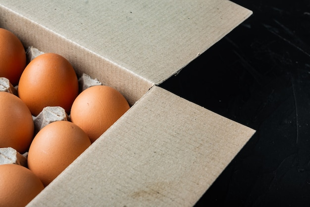 Braune eier im kartonfach, auf schwarzem hintergrund, mit platz für textkopyspace