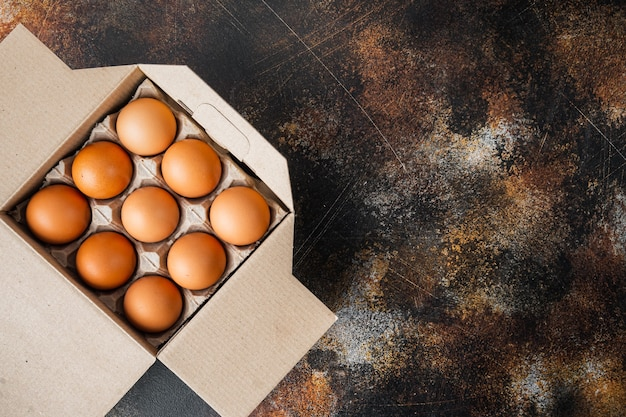 Braune eier im kartonfach, gesetzt auf altem dunklem rustikalem hintergrund, draufsicht flache lage, mit platz für textkopyspace