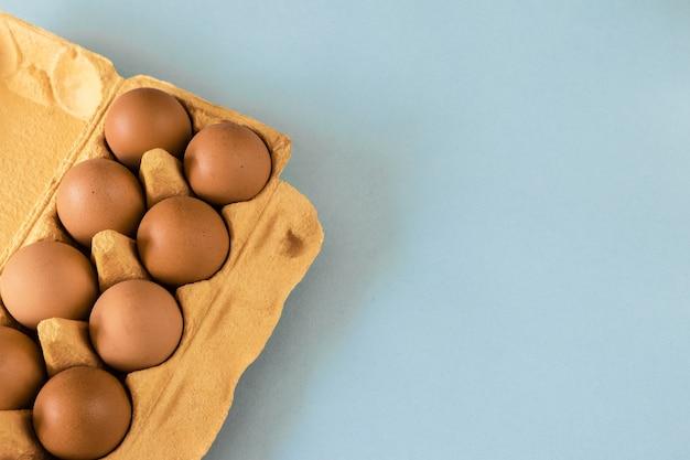 Braune eier im kasten auf blauem hintergrund
