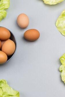 Braune eier in grauer keramikschale. kohlblätter und zwei eier auf dem tisch. speicherplatz kopieren